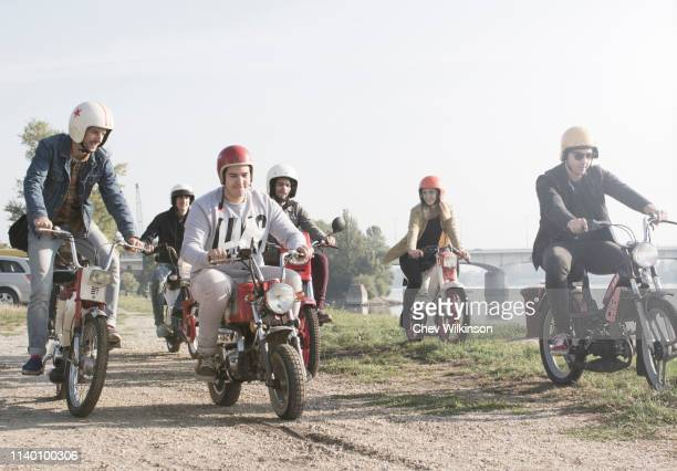 group of friends riding mopeds beside lake - mobylette photos et images de collection