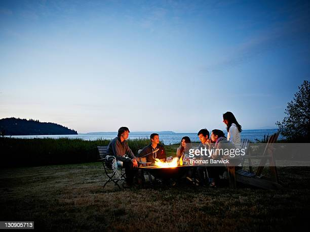 group of friends roasting hot dogs at dusk - campfire stock pictures, royalty-free photos & images
