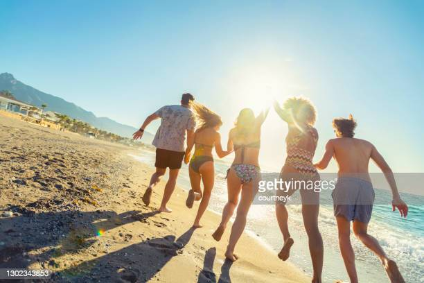 group of friends running and jumping into the ocean at sunset. - spain stock pictures, royalty-free photos & images