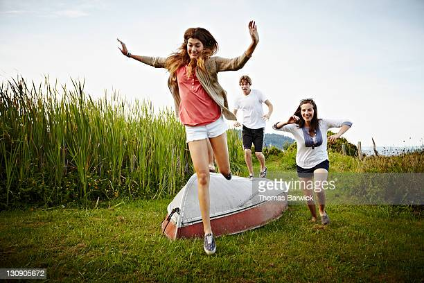 Group of friends running and jumping over boat