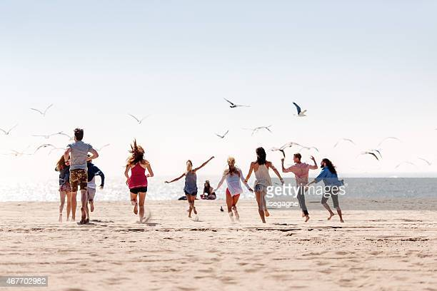 Group of friends running at the beach