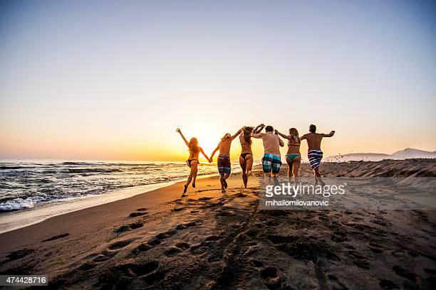 Groupe d'amis courir sur la plage