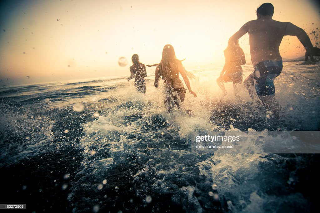Group of friends running into the water : Stock Photo