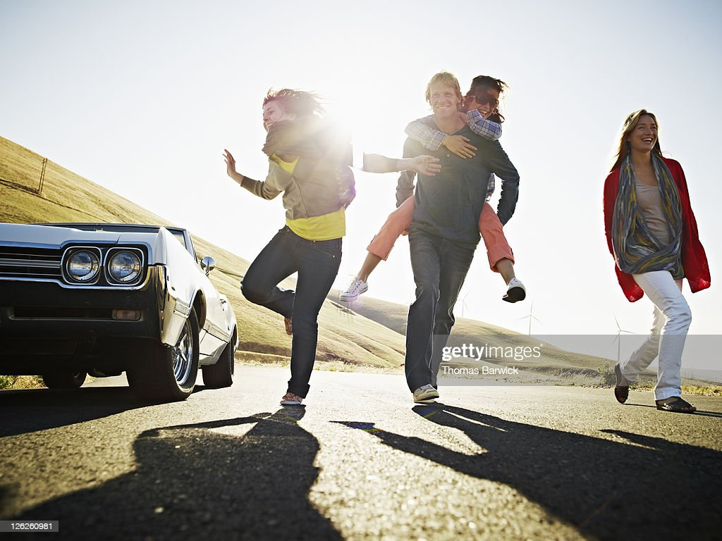 Group of friends running on empty road : Stockfoto