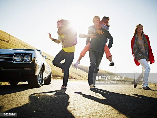 Group of friends running on empty road