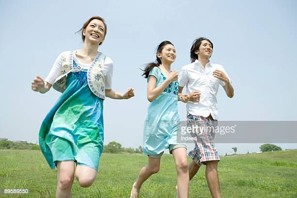 Group of friends running on grass, smiling