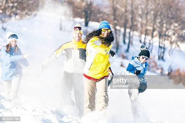 Group of friends running on snow path