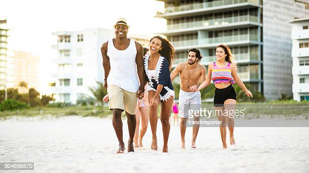 group of friends running on the beach of miami beach - skinny man fat woman stock pictures, royalty-free photos & images