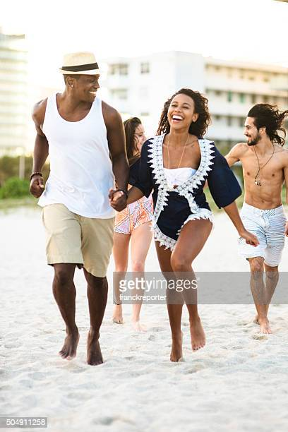 group of friends running on the beach of miami beach - fat man on beach stock photos and pictures