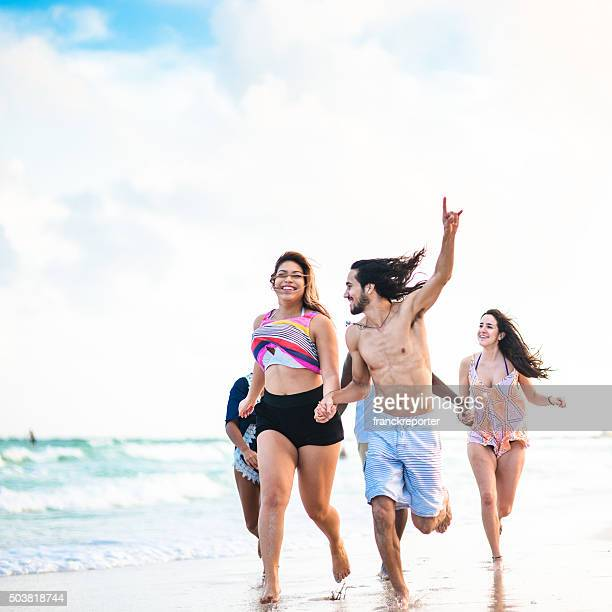 group of friends running on the beach - fat guy on beach stock pictures, royalty-free photos & images