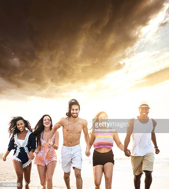 group of friends running on the beach - skinny man fat woman stock pictures, royalty-free photos & images