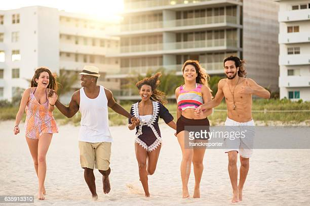group of friends running on the beach - fat man on beach stock photos and pictures