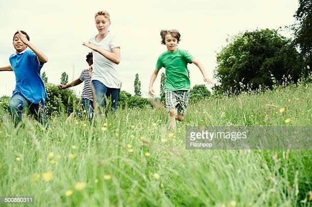 Group of friends running through a field