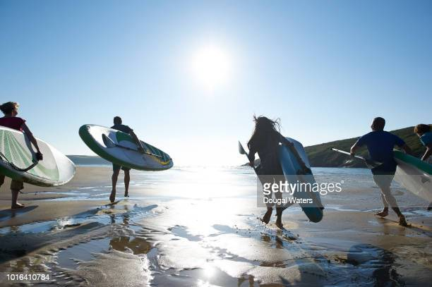 group of friends running to sea with sup paddle boards. - dougal waters stock pictures, royalty-free photos & images