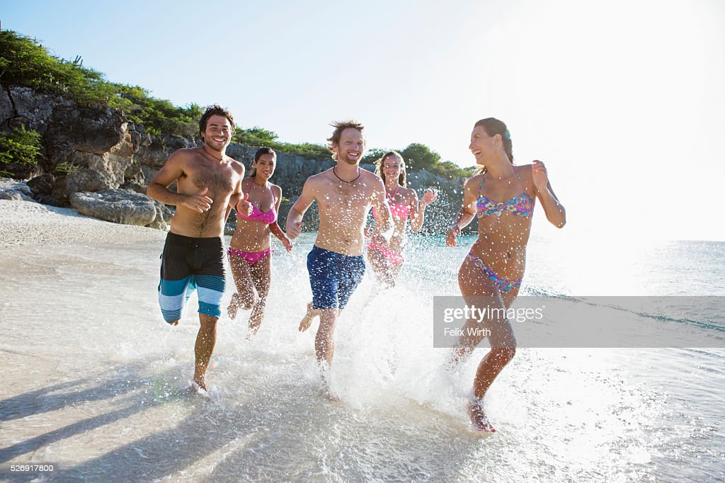 Group of friends running together along sandy beach : Stockfoto
