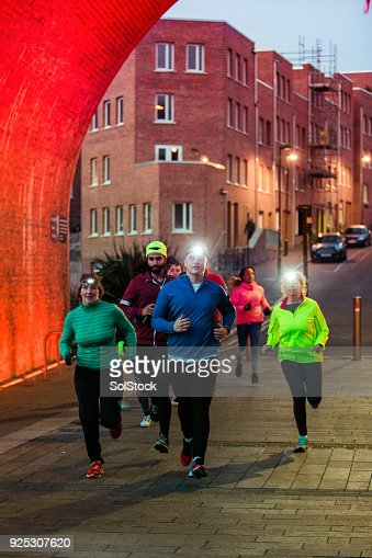 Group Of Friends Running Together At Night