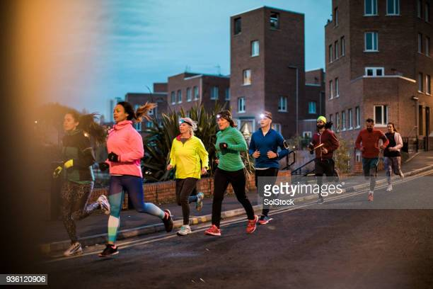 group of friends running together at night - organised group stock pictures, royalty-free photos & images