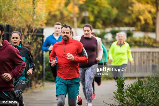 group of friends running together - organized group stock pictures, royalty-free photos & images