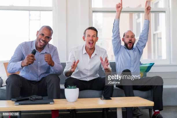 Group of friends sat watching sports on TV after work