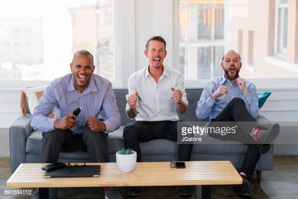 Groupe d'amis assis sports regarder à la télévision après le travail