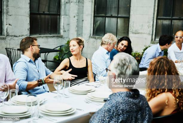 Group of friends seated at table on restaurant patio for celebration dinner
