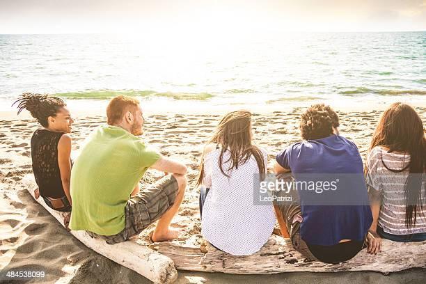 Groupe d'amis assis en face de la mer
