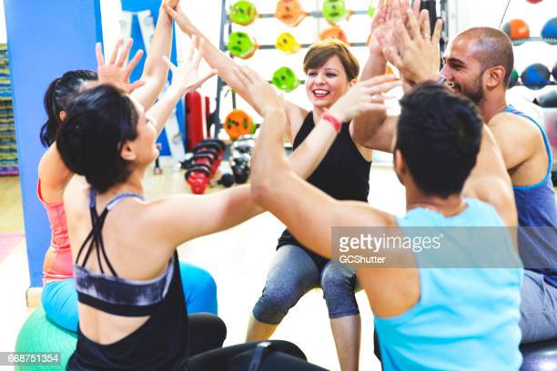 Group of friends seated on swiss exercise balls and cheering together