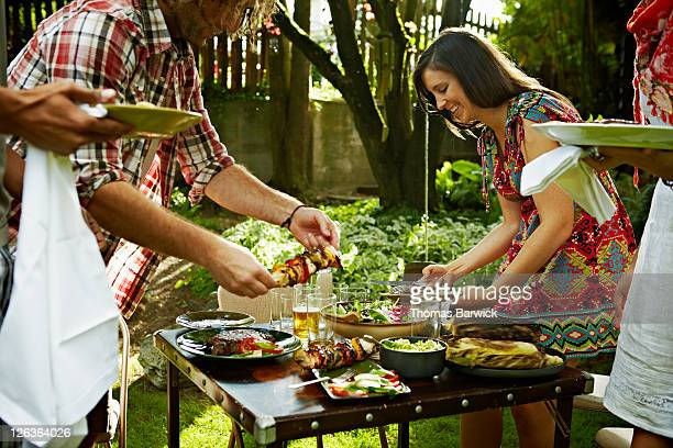 Group of friends serving food at table in garden
