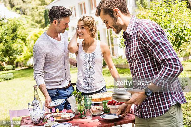 Group of friends setting up garden party