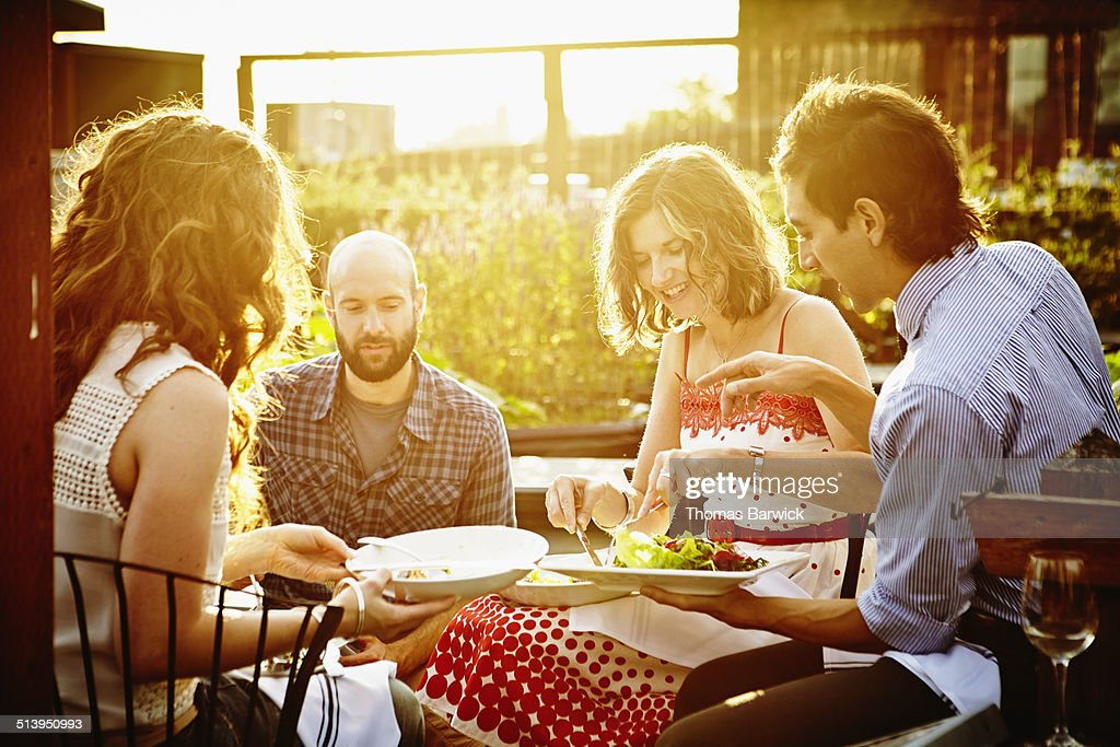 Group of friends sharing dinner at sunset : Stock Photo