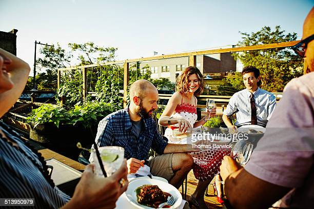 Group of friends sharing dinner in rooftop garden