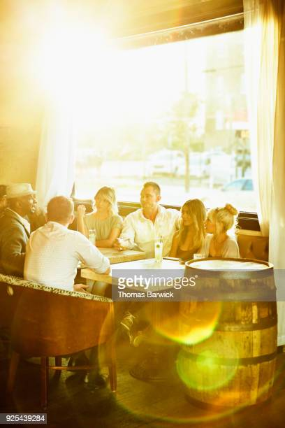 Group of friends sharing drinks at table in bar