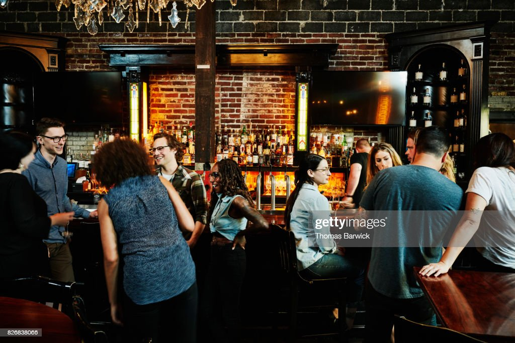 Group of friends sharing drinks in busy bar : Stock Photo