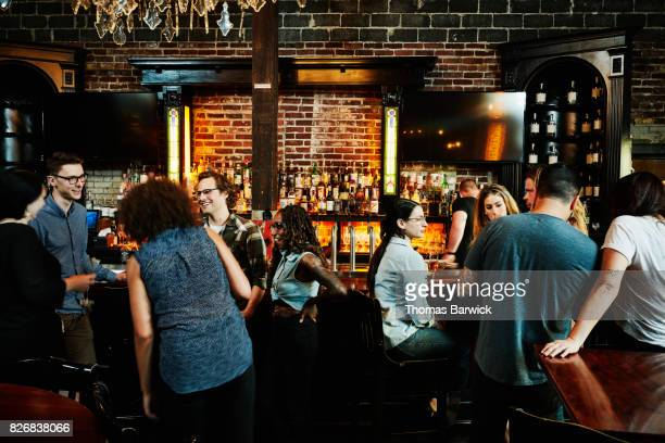 Group of friends sharing drinks in busy bar