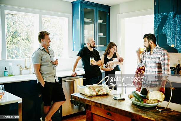 Group of friends sharing drinks in kitchen