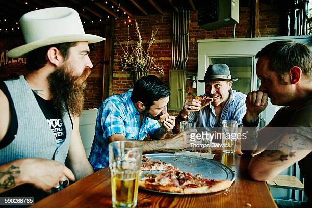 Group of friends sharing pizza and beers