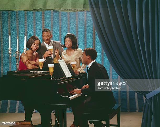 A group of friends sing along at a piano as they enjoy tall glasses of beer in a staged setting 1960s