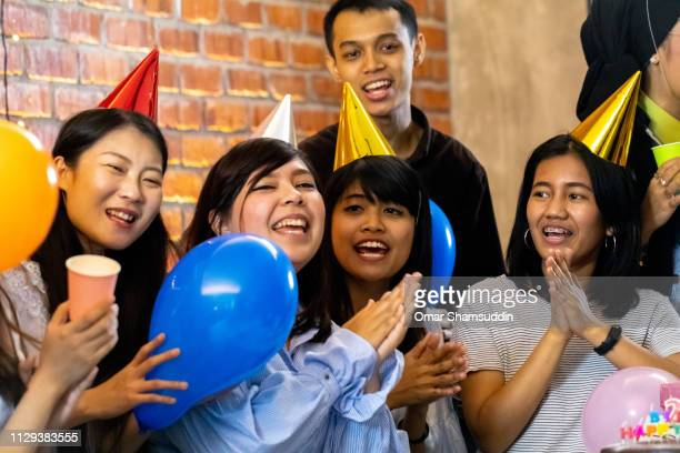 Group of friends singing birthday song and clapping
