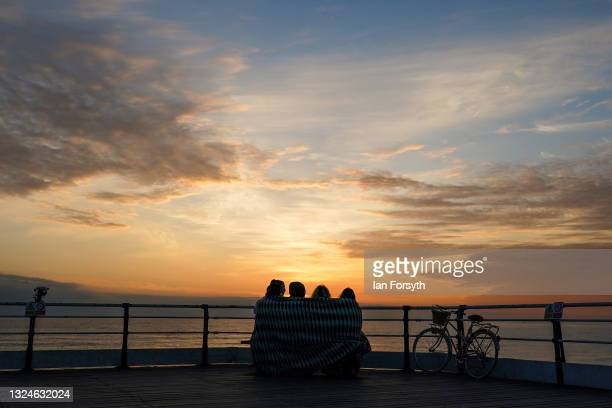 Group of friends sit and watch the sunrise on the morning of the summer solstice at Saltburn pier on June 21, 2021 in Saltburn-by-the-Sea, England....
