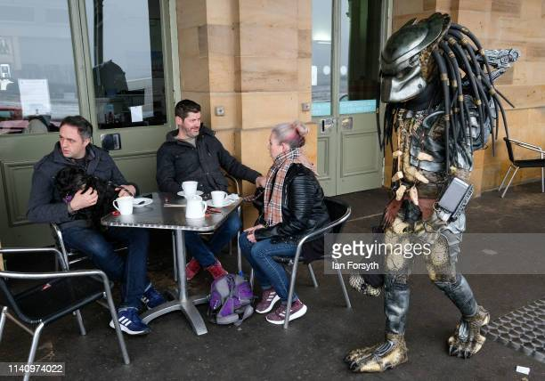 Group of friends sit in a cafe as a man dressed as Predator walks past on the second day of the Scarborough Sci-Fi weekend held at the seafront Spa...