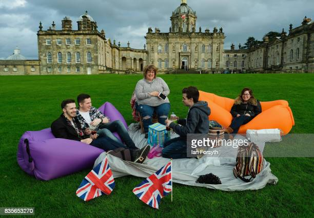 A group of friends sit on inflatable chairs as they attend the annual Castle Howard Proms Spectacular concert held on the grounds of the Castle...