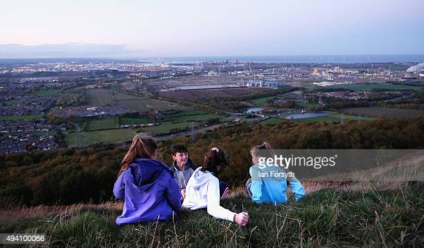 A group of friends sit overlooking Teesside during a torchlit procession on the top of the Eston Hills on October 24 2015 in Eston Cleveland The...