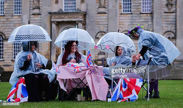 A group of friends sit under umbrellas during a rain shower at the annual classical Proms Spectacular concert held on the north lawn of Castle Howard...