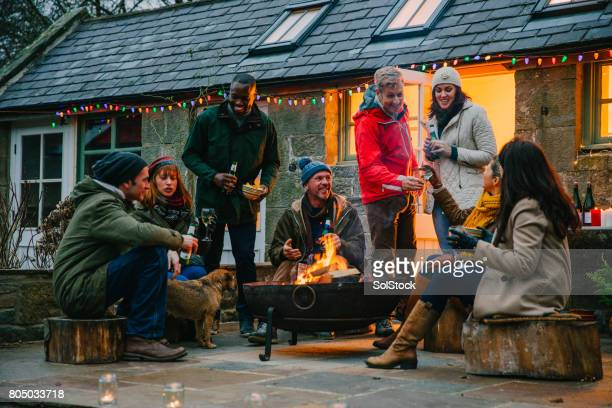 group of friends sitting around a fire pit - fire pit stock pictures, royalty-free photos & images