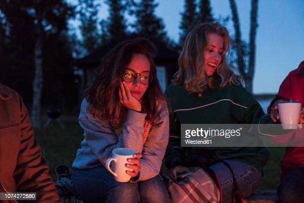 group of friends sitting at a campfire, talking and drinking tea - norrbotten province stock pictures, royalty-free photos & images