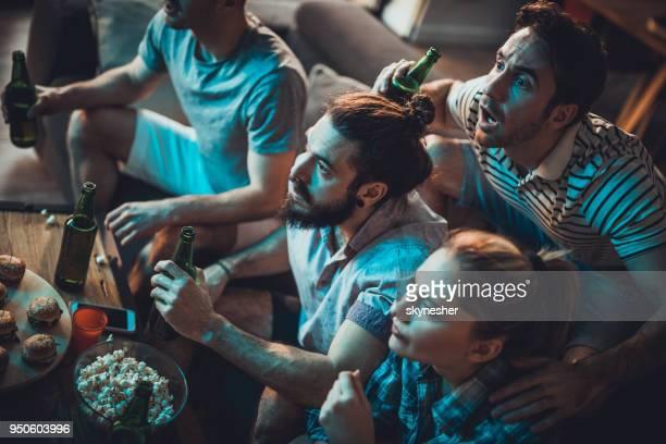 grupp av vänner sitter hemma och tittar på en sportspel i misstro. - friendly match bildbanksfoton och bilder