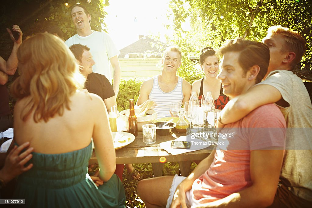 Group of friends sitting at table in backyard : Stock Photo