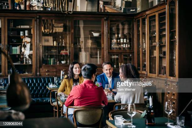 group of friends sitting at table in fancy restaurant - quattro persone foto e immagini stock