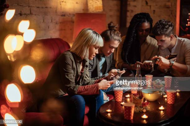 Group of friends sitting at the party and using smartphones