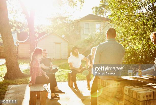 Group of friends sitting in backyard on sunny summer evening